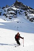 A young woman skis down a slope with telemark skis, Rila Mountains, Bulgaria