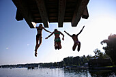 Three girls jumping off into the lake from a wooden diving platform, Utting, Ammersee, Bavaria, Germany