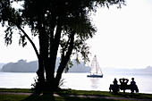 Three people sitting on a park bench on the island Frauenchiemsee, Fraueninsel on Lake Chiemsee, Bavaria, Germany