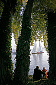 Father and Child watching sailing boats on the island Frauenchiemsee, Fraueninsel on Lake Chiemsee, Bavaria, Germany