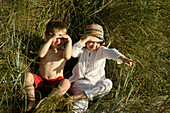 Girl and boy sitting on beach grass, Travemuende Bay, Schleswig-Holstein, Germany