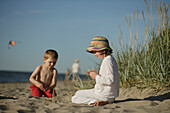 Girl and boy playing on sandy beach of Baltic Sea, Travemuende Bay, Schleswig-Holstein, Germany