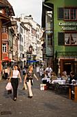 Two women strolling over Augustinergasse, passing a pavement cafe, Zurich, Canton Zurich, Switzerland