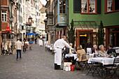 Waiter serving a drink in a pavement cafe, view inside Augustinergasse with ornated bay windows, Zurich, Canton Zurich, Switzerland