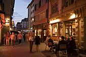 People sitting in a small pavement cafe in the late evening near Hirschenplatz, Niederdorfstrasse, Zurich, Canton Zurich, Switzerland
