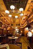 Woman walking through restaurant Bierhalle Kropf (Beer Hall Kropf) with a nice decorated Art Nouveau ceiling, Zurich, Canton Zurich, Switzerland