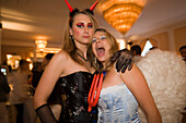 Portrait of two girls dressed up as angel and devil in the louge of the Baur au Lac Hotel, After Party of the Street Parade (the most attended technoparade in Europe), Zurich, Canton Zurich, Switzerland