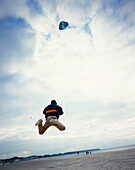 Young man with nasa wing stunt kite, beach of Warnemuende, Mecklenburg-Western Pomerania, Germany