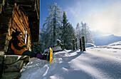 Wanderer mit Schneeschuhen bei Pause vor verschneiter Almhütte, Priesbergalm, Berchtesgadener Alpen, Oberbayern, Bayern, Deutschland