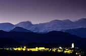 City of Anisa during nighttime with illuminated castle and range of snow covered Pyrenees, Anisa, Pyrenees, Spain