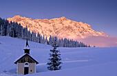 Snow covered chapel with Hochkoenig in afterglow, Maria Alm, Salzburg, Austria