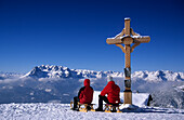 Two persons sledging at cross of Bischlinghöhe, view to Hochkönig range, skiing area Werfenweng, Salzburg, Austria