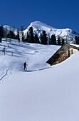 Back country skier in front of alpine hut, ascend to Wagendrischlhorn, Reiteralm Range, Berchtesgaden, Upper Bavaria, Bavaria, Germany