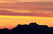 Silhouette of Kampenwand in front of a glowing sky, Chiemgau, Upper Bavaria, Bavaria, Germany