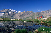 Three hikers resting at mountain lake, mountains Piz Palue and Bellavista in background, Bernina, Upper Engadin, Grisons, Switzerland