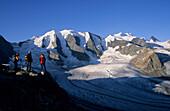 Three alpinists enjoying view to mount Piz Palue and glacier of Pers, Bernina, Upper Engadin, Grisons, Switzerland