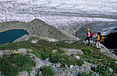 Two mountaineerers on a moraine of Isla Pers above a glacier lake and Morteratsch glacier, Bernina, Oberengadin, Grisons, Switzerland