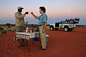 Two men, a local nature guide and a tourist bring a toast on the sundawn. Gondwana Kalahari Park, Namibia, Africa. MR of tourist.