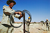 An old man and employee of the namib desert lodge dimantels a fence. His work belongs to the environmental program Fence Free Namibia. It will allow animals to migrate again free through the desert. Gondwana Namib Desert park. Namib Desert. Southern Nambi