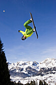 A young man on a snowboard doing a backflip in the funpark snowland, Wildhaus, Toggenburg region, East Switzerland, St. Gallen, Switzerland, Alps, Europe