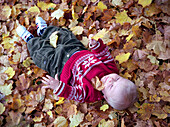 Little boy lying in heap of leaves