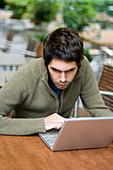 Young man sitting in a pavement cafe using a laptop