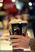 Male hand holding a popcorn carton