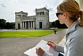 Young woman drawing Propylaea, Koenigsplatz, Munich, Bavaria, Germany