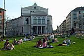 People sunbathing on Gaertnerplatz (square), Munich, Bavaria, Germany