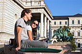 Couple sitting in front of Academy of Fine Arts, Munich, Bavaria, Germany