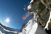Skier jumping over rock, Falkertsee, Carinthia, Austria