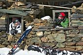 Two snowboarder looking through windows of derelict cabin, Falkertsee, Carinthia, Austria