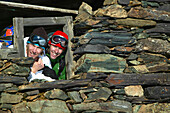Two snowboarder looking through window of derelict cabin, Falkertsee, Carinthia, Austria
