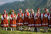 Singing women in traditional costumes at Rose Festival, Karlovo, Bulgaria, Europe