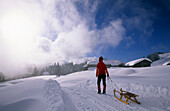 Young woman pulling a sledge on tobbogan run near hut Lustenauer Huette, Schwarzenberg, Bregenzer Wald, Vorarlberg, Austria