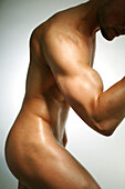 Naked young man flexing muscles