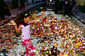 Child playing with blossoms, La Laguna, Tenerife, Canary Islands, Spain