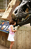 A child looking at a sculpture of a dinosaur in Washington Zoo, Washington DC, United States, USA