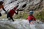 Men glinding through river, swim and hike canyon Raebloch, Emmental valley, Canton of Bern, Switzerland, MR
