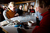 Group of young woman playing memory, Tracuit hut, Pennine Alps, canton of Valais, Switzerland, MR