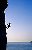 Young woman climbing at rock face over Aegean Sea, Kalymnos Island, Greece, MR
