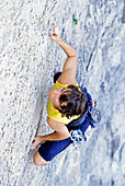 Young woman freeclimbing on rock, European Alps, MR