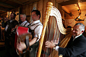 Mature man plays the Harp with  his Folkmusic Band in the Lounge of the  Viehausalm, Nationalpark Hohe Tauern, Salzburger Land, Austria