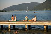 Four young women sunbathing on boardwalk, Lake Ossiach, Ossiach, Carinthia, Austria