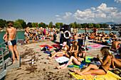 Young people sunbathing on landing stage at Strandbad Klagenfurt, Lake Wörthersee (biggest lake of Carinthia), Klagenfurt, Carinthia, Austria