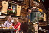 Couple listening to man playing accordion, Lammersdorf hut, Lammersdorf near Millstatt, Carinthia, Austria