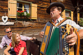 Couple listening to musician playing accordion, Steirische Accordion, Lammersdorfer Hut, 1650 m, Lammersdorf near Millstatt, Carinthia, Austria