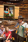 Couple listening to Hans Werner Schmölzer (innkeeper of Lammersdorfer Hütte) playing accordion (called Steirische), young woman looking from a window, Lammersdorfer Hütte (1650 m), Lammersdorf near Millstatt, Carinthia, Austria