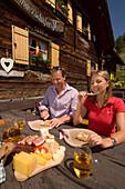 Couple eating a Jause (snack) at Lammersdorfer Hütte (1650 m), Lammersdorf near Millstatt, Carinthia, Austria