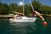 Couple jumping from a sailing boat into Millstätter See (deepest lake of Carinthia), Millstatt, Carinthia, Austria